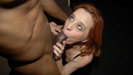 Red mature slut munching on a big black cock