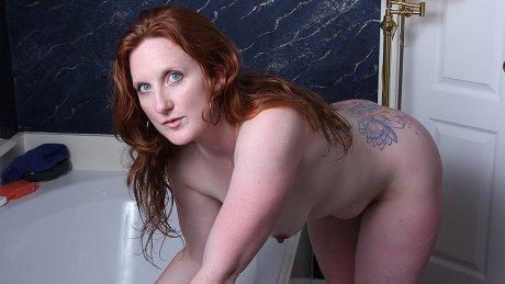 Sexy American redhead enjoys her toy in the bathtub